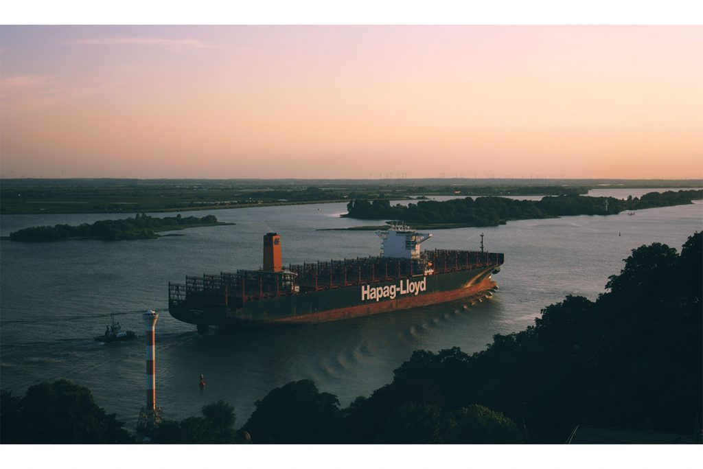 Containerschiff auf der Elbe bei Sonnenuntergang